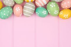 Easter egg top border against pink wood Royalty Free Stock Images