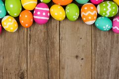 Easter egg top border against rustic wood Stock Images