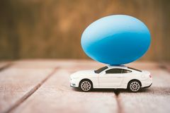 Easter egg and toy car on wooden background royalty free stock image