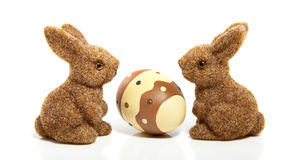 An easter egg between two bunnies. Isolated on white royalty free stock photography