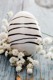 Painted easter egg with black stripes on blue wooden table and with white flowers. Easter egg white with black stripes and white flowers  on blue wooden table Royalty Free Stock Photos