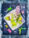 Easter egg in white tray with holiday decoration and hyacinth flowers on blue wooden background Royalty Free Stock Images