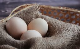 Easter egg in a wicker basket an old wood background royalty free stock image