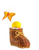 Easter egg in wicker shoe on a white background. Yellow Easter egg in wicker shoe and orange butterfly on a white background Stock Photos