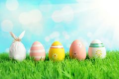 Easter egg wrapped in a paper in the shape of a bunny with colorful Easter eggs on green grass. Spring holidays concept stock image