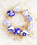 Easter egg wreath on a white wooden background. Stock Photo