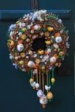 Easter egg wreath on wooden door. Easter egg wreath on a dark blue wooden door background royalty free stock image