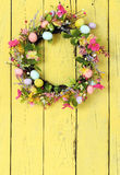 Easter egg wreath. On a yellow wooden background stock images