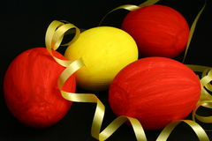 Easter Eggs. Three red and one yellow egg with a yellow ribbon on a black background Stock Images