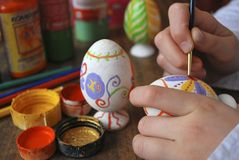 Easter eggs. The girl enterring wooden egg, hands and paints Stock Photography