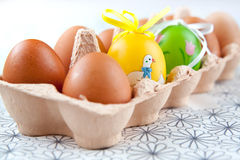 Easter eggs. Painted Colorful Easter Eggs with normal eggs in a set Royalty Free Stock Images