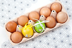 Easter eggs. Painted Colorful Easter Eggs with normal eggs in a set Royalty Free Stock Photo