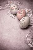 Easter eggs. Three decorated Easter eggs with flowery ribbon over grunge background in old pink color Stock Photos