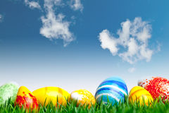Easter eggs. In green grass over blue sky with clouds