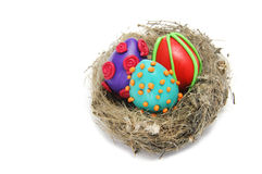 Easter eggs. Some plasticine easter eggs of different colors in a nest isolated on a white background Stock Photography