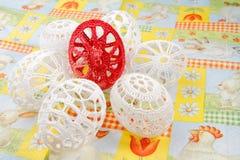 Easter eggs. Crocheted white easter eggs around red egg Royalty Free Stock Image