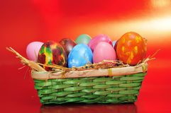 Easter eggs. A basket with some easter eggs of different on a red background Stock Photo