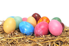 Easter eggs. Some easter eggs of different colors with straw on a white background Stock Photo