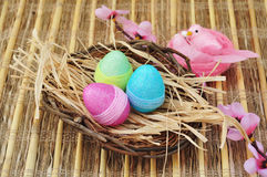 Easter eggs. Wicker basket with easter eggs, pink flowers and birds over rustic background Royalty Free Stock Photography