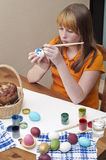 Easter eggs 2. The redhead girl is painting Easter eggs Stock Photo