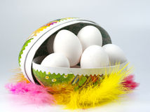Easter eggs. Closeup of white eggs in an Easter egg surrounded by colorful feathers Royalty Free Stock Photos
