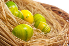 Easter eggs. Hand painted green and yellow colorful Easter eggs arranged with natural hay Stock Photos