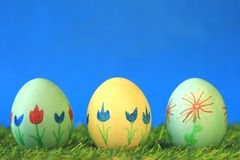 Easter eggs. Three Easter eggs, painted with colorful flowers, against a blue background Stock Image