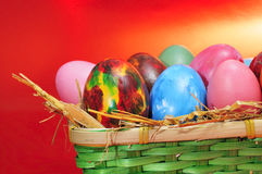 Easter eggs. Some easter eggs of different colors in a basket on a red background Royalty Free Stock Photo