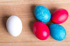 Easter eggs. Four colored Easter eggs and white, on a piece of wood Royalty Free Stock Image