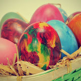 Easter eggs. Some easter eggs of different colors on a basket with straw, with a retro effect Royalty Free Stock Images