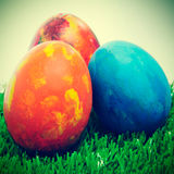 Easter eggs. Some easter eggs of different colors on the grass, with a retro effect Royalty Free Stock Image
