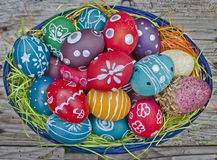 Easter eggs. Colorful hand drawn Easter eggs in blue basket on wooden background Stock Photography