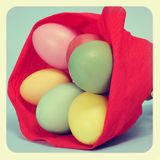 Easter eggs. Some easter eggs of different colors wrapped with red crepe paper as in a bouquet, with a retro effect Royalty Free Stock Photography