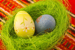 Easter eggs. Colored Easter eggs in small basket with grass Stock Image