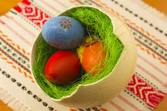 Easter eggs. Colored Easter eggs in one big ostrich egg with grass Stock Photo