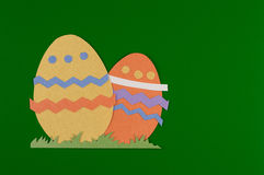 Easter eggs. Colorful eggs with grass and cut on paper, easter egg on a red background royalty free stock photo