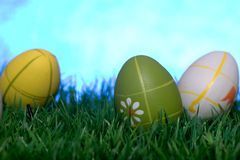 Easter eggs. Three colored easter eggs lying in the grass against a blue background Stock Image