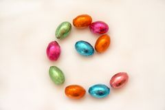 Easter Eggs. In bright colourful wrap spelling out the letter e either for childhood spelling or to show ecommerce in spring Royalty Free Stock Photo