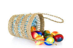 Easter eggs. Basket with boiled colorful painted Easter eggs on white background, reflective surface Stock Photo