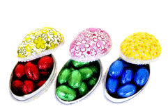 Easter eggs. Colorful wrapped chocolate Easter eggs on white background, reflective surface Stock Images