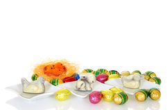 Easter eggs. Colorful wrapped chocolate Easter eggs on white background, reflective surface Stock Photography