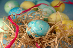 Easter Eggs. A blue Easter egg in a raffia nest with a pink raffia ribbon Royalty Free Stock Photo