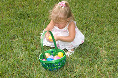 Easter Eggs. Adorable Little Girl Playing with Easter Eggs in Basket Royalty Free Stock Images