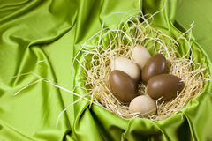Easter eggs. Wooden and chocolate easter eggs placed in a decorative nest, green satin background Royalty Free Stock Images