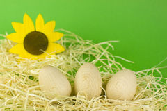 Easter eggs. Three plain wooden easter eggs lying in a decorative nest with a wooden sun flower and green background Royalty Free Stock Photos