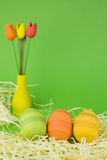 Easter eggs. Hand painted easter eggs with a wooden tulips  on green background - easter theme in green, yellow, red and orange Stock Photography
