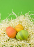 Easter eggs. In green, yellow and orange in a decoration nest on a green background Royalty Free Stock Image