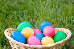 Easter Eggs. Basket of brightly colored easter eggs sitting outside in the grass Stock Photo