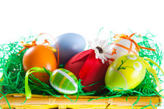 Easter eggs. Close up of colorful decorated Easter eggs in nest basket, isolated on white background Royalty Free Stock Photo