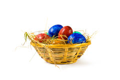 Easter eggs. Red, blue, yellow and green easter eggs in a basket, isolated on white background stock photos